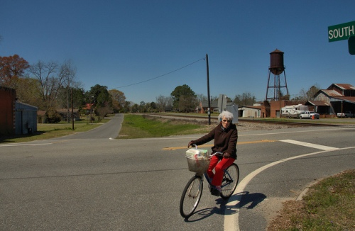 Railroad Avenue Chauncey GA Dodge County Cool Lady Riding Bicycle Water Tower Cotton Gin Warehouse Store Photograph Copyright Brian Brown Vanishing South Georgia USA 2014